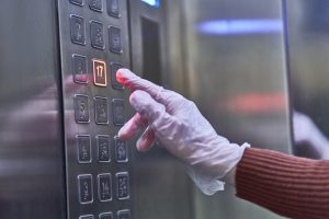 gloved hand touching elevator button